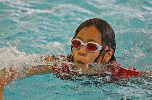Child learning to swim as part of Harris County Aquatics Program