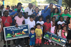 Commissioner Ellis with families 'doubling up' their SNAP purchases at farmers markets