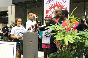 Commissioner Ellis lighting the torch for the Street Olympics